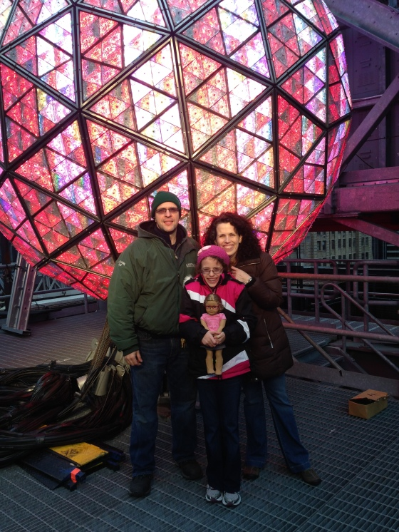 Family shot in front of the New Year's Eve Ball.