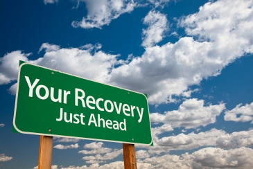 Your Recovery Green Road Sign Over Dramatic Clouds and Sky.